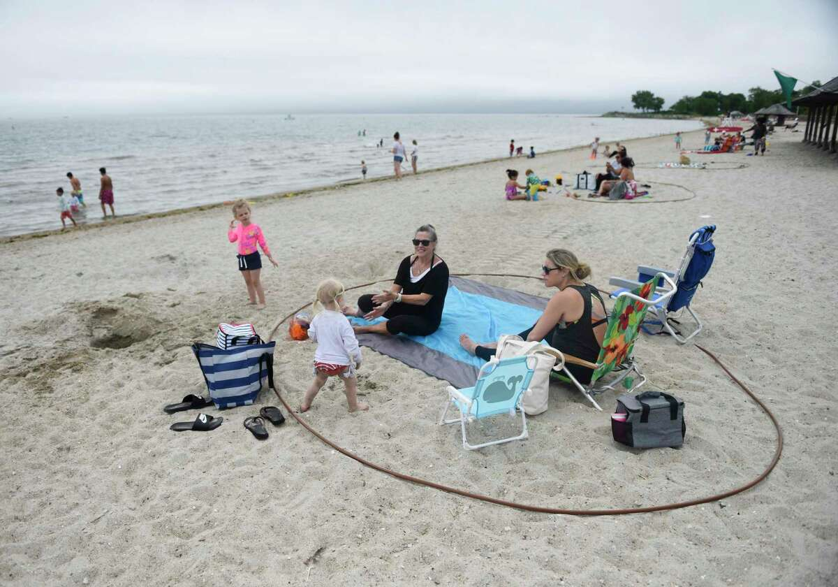 Greenwich grandmother Kathleen Hufnagel, mother Shanna Licitra, and daughter Gianna, 2, lounge inside a large rubber circle to promote social distancing on the beach at Greenwich Point Park in Old Greenwich, Conn. Thursday, June 18, 2020. The town's beaches have been open to swimmers for a week now and steps are in place to maintain social distancing in the sand.