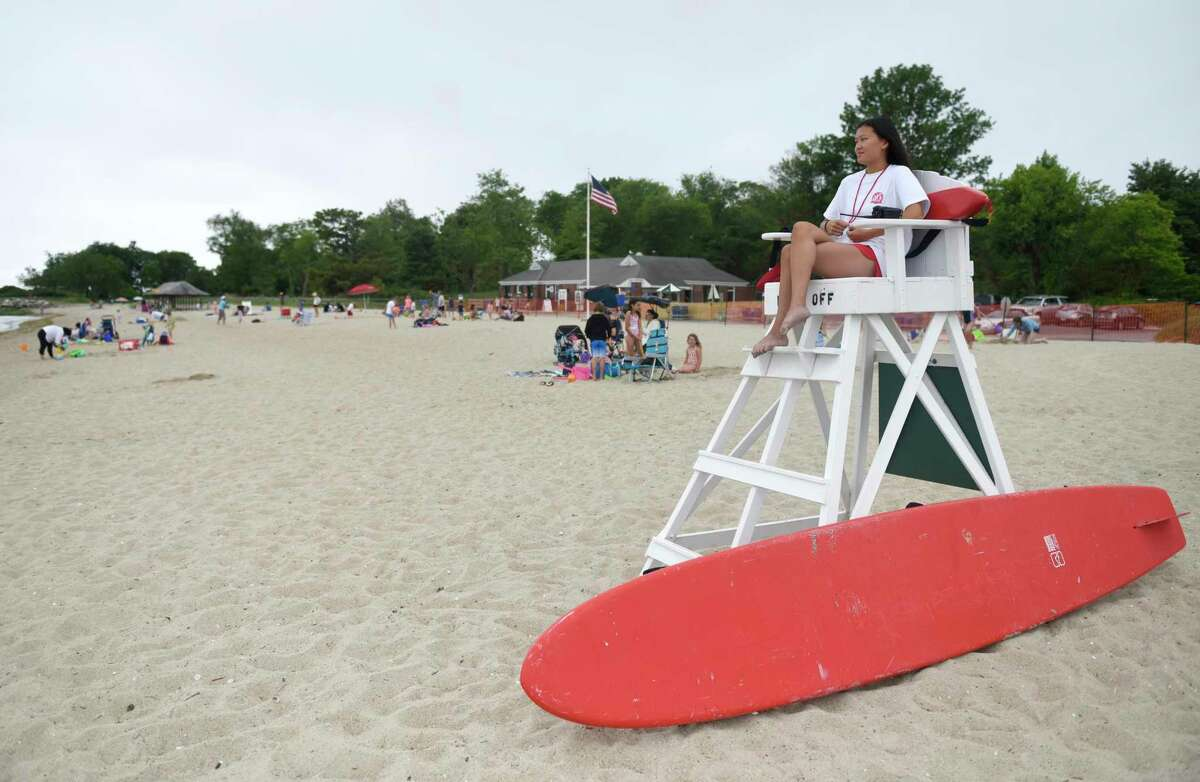 Lifeguard Nika Sibley watches over swimmers on the beach at Greenwich Point Park in Old Greenwich, Conn. Thursday, June 18, 2020. The town's beaches have been open to swimmers for a week now and steps are in place to maintain social distancing in the sand.