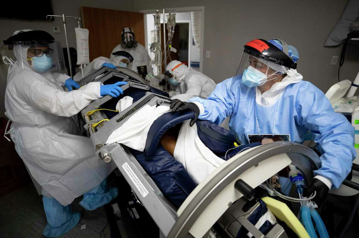 The medical staff at United Memorial Medical Center rotate a patient to face upward before trying to establish a dialysis line on Thursday, June 11, 2020, in Houston. The bed keeps the patient immobile so they could be flipped downward, helping his blood oxygen levels. The state of Texas has seen a spike in COVID-19 cases.