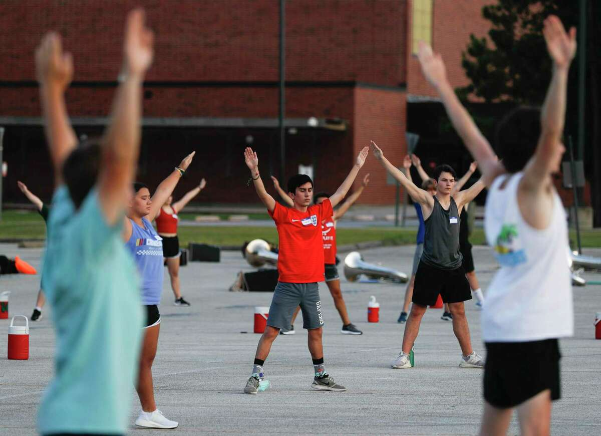 Members of The Woodlands High School marching band take part in visual warm-ups before practice, Wednesday, June 17, 2020, in The Woodlands. Students were able to participate under social distancing guidelines and with regular disinfecting of equipment, according to regulations set by the University Interscholastic League.
