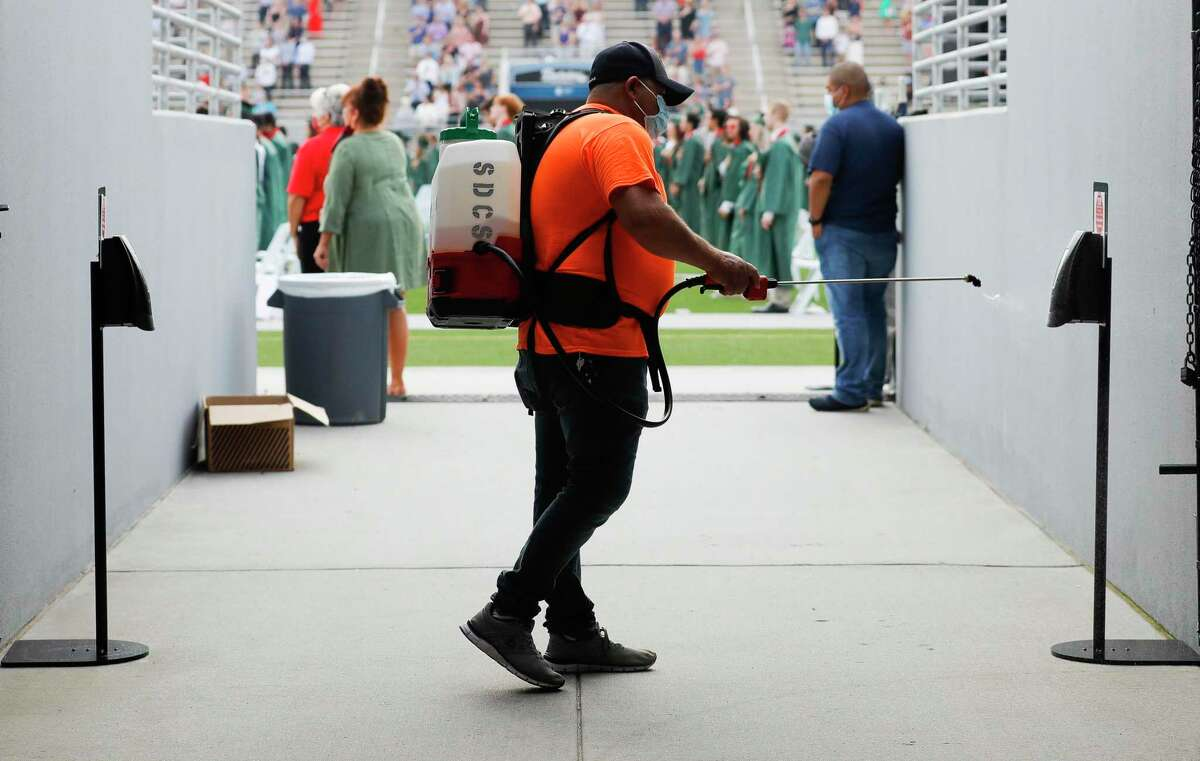 Custodian Jose Morreno sprays handrails and other high-touch surfaces with disinfectant during The Woodlands High School's graduation ceremony at Woodforest Bank Stadium, Tuesday, June 2, 2020, in Shenandoah. On June 23, TEA will release its guidelines to schools for next year, which is likely to include disinfecting regulations like those used for graduation ceremonies.