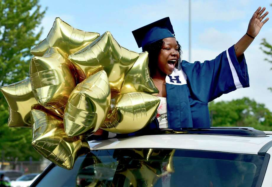 New Haven, Connecticut -Thursday, June 18, 2020: Senior Ashanti Payne waves as she arrives for the start of the Hillhouse High School graduation in the Bowen Field parking lot in Wednesday evening in New Haven. Because of the Covid-19 pandemic, the school used cars as the vehicle for social-distancing to get the seniors to the stage and get their high school diplomas. Photo: Peter Hvizdak / Hearst Connecticut Media / New Haven Register