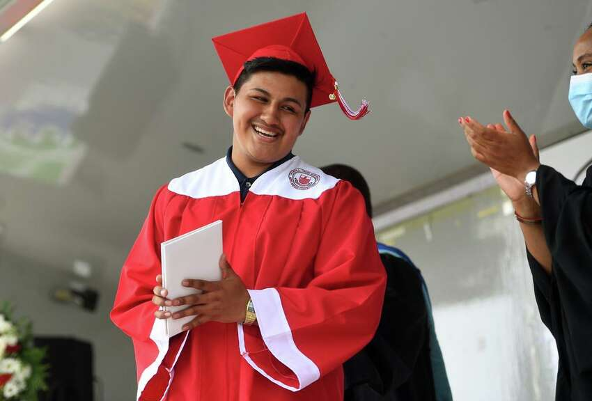 Cesar Tlecuitl smiles as he receives his diploma during the Wilbur Cross High School drive up graduation ceremony at Lighthouse Point Park in New Haven, Conn. on Thursday, June 18, 2020.