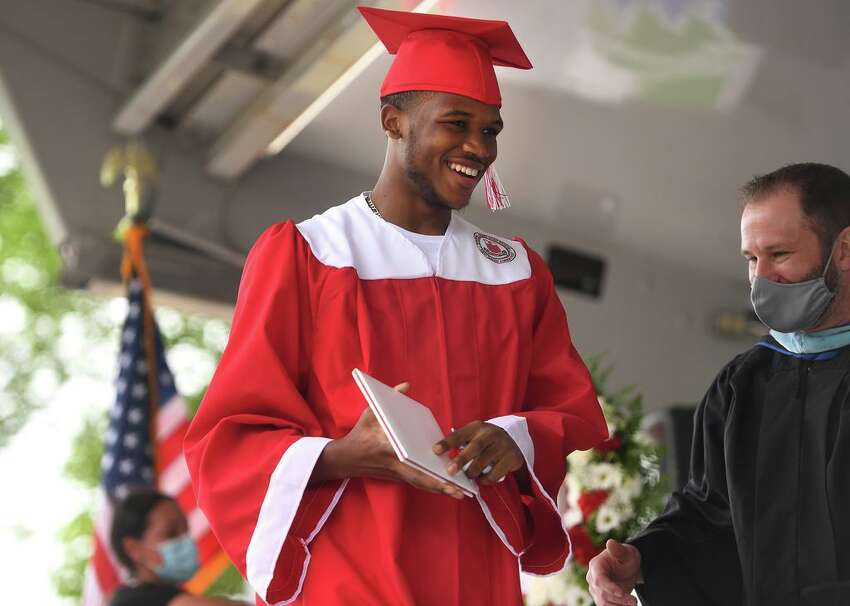 Jaleem Sayles smiles as he receives his diploma during the Wilbur Cross High School drive up graduation ceremony at Lighthouse Point Park in New Haven, Conn. on Thursday, June 18, 2020.