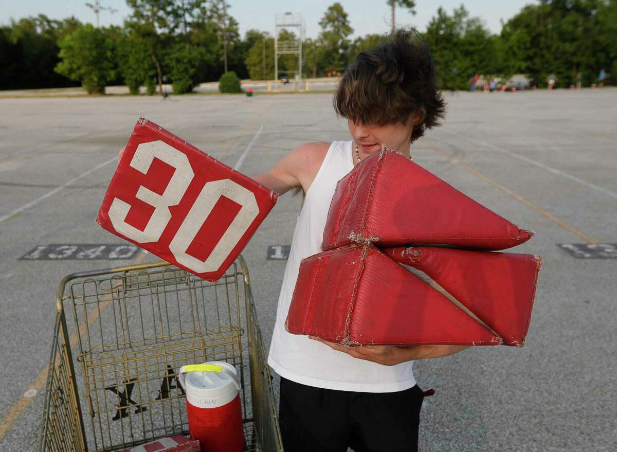 Wyatt McGlaun helps put out yard line markers during marching band practice at The Woodlands High School, Wednesday, June 17, 2020, in The Woodlands. Students were able to participate under social distancing guidelines and with regular disinfecting of equipment, according to regulations set by the University Interscholastic League.