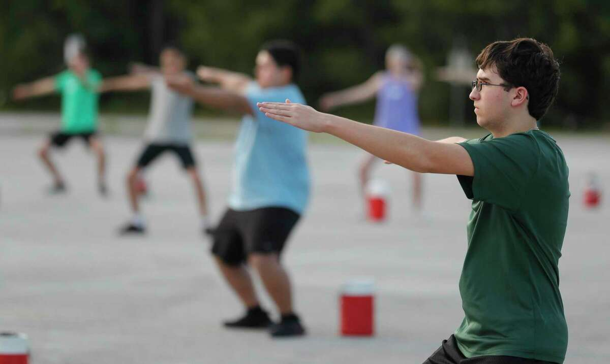 Nico Rodriguez, right, takes part in visual warm-ups during marching band practice at The Woodlands High School, Wednesday, June 17, 2020, in The Woodlands. Students were able to participate under social distancing guidelines and with regular disinfecting of equipment, according to regulations set by the University Interscholastic League.