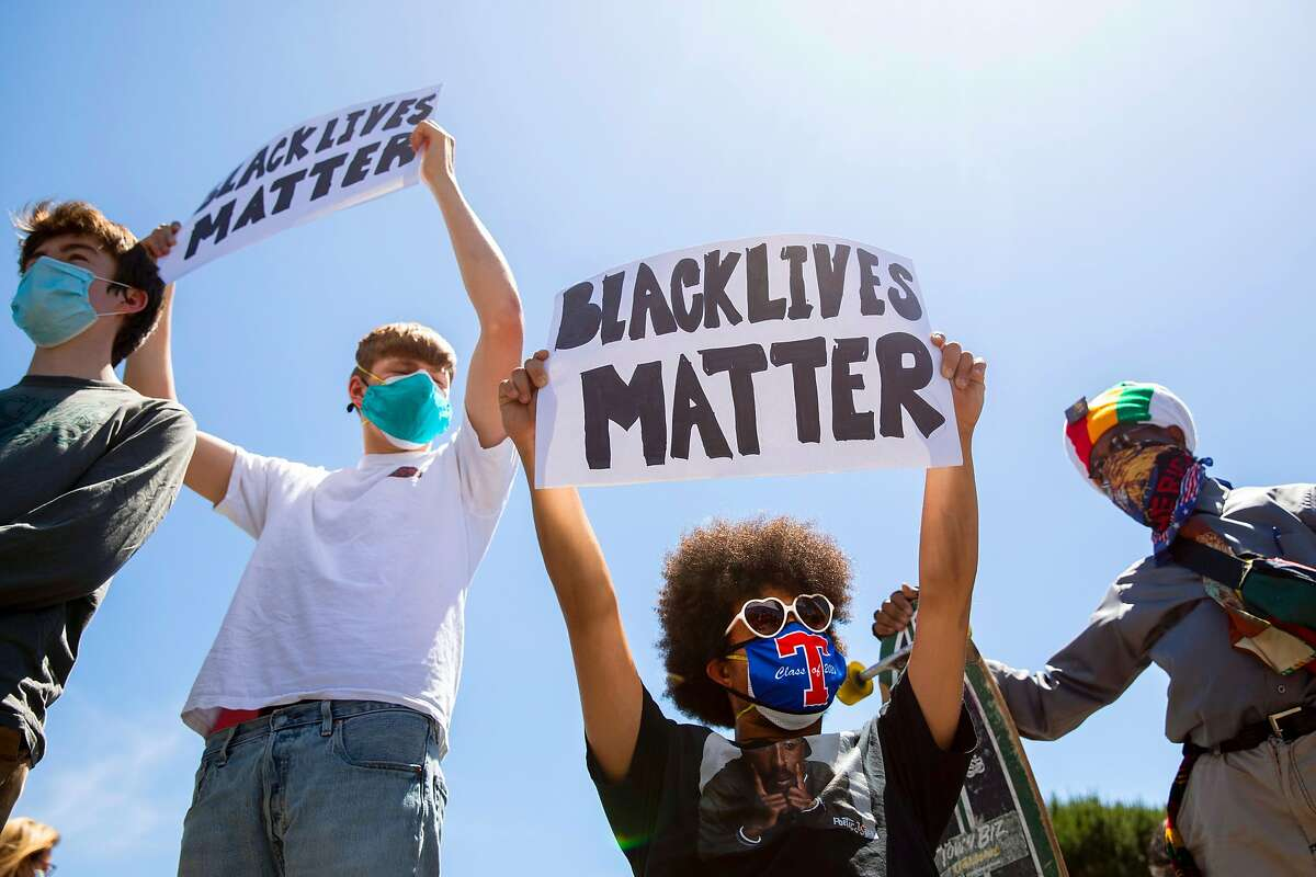 (From left) Kai Cunha, 18, Mark Harmon, 16, Garnett Silver-Hall, 18, and Garnett's father Zulu Hall carry protest signs while participating in a Black Lives Matter demonstration with his friends in Marin City, Calif. Tuesday, June 2, 2020. The death of George Floyd in Minneapolis has sparked international demonstrations in support of Black lives and has affected Garnett greatly. This moment has inspired him to participate in protests, use his social media platform to educate his followers and actively engage in the Black Lives Matter movement.