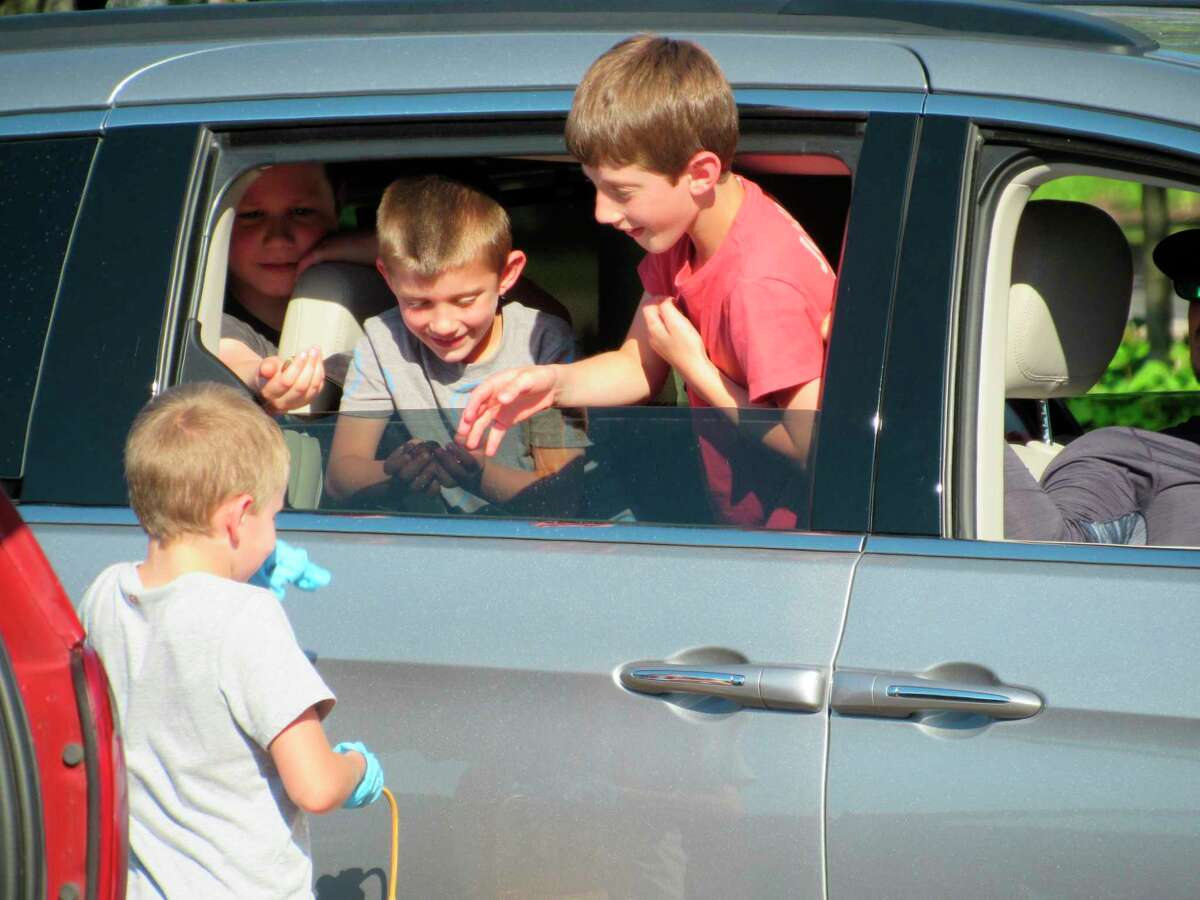 A member of the VBS team passes out coins in a reenacting of a biblical story during Midland First United Methodist Church's drive-in VBS on Wednesday, June 17. (Victoria Ritter/vritter@mdn.net)