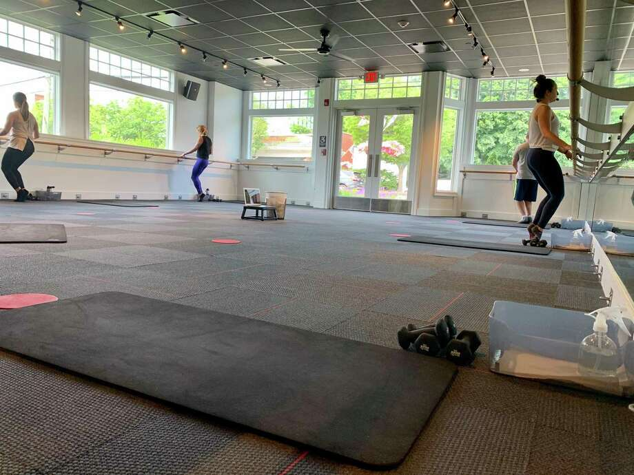 Emily Fisher, lead teacher at Pure Barre in Darien, teaches a classic barre class Wednesday with clients spaced 12 feet apart. The class is also streamed live on Zoom for members who choose not to come into the studio. Photo: Contributed Photo / / Connecticut Post