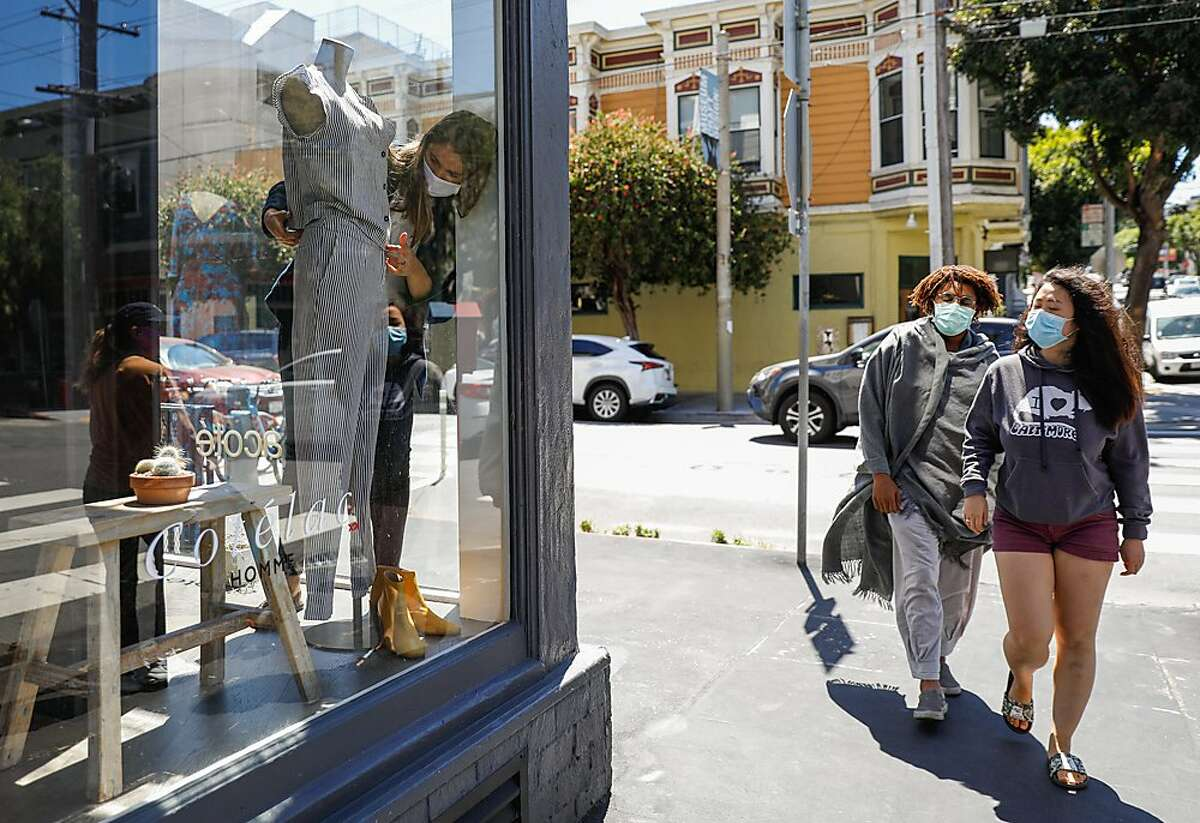 Store manager Kathryn Sandretto (left) changes out the mannequin at Acote boutique as people walk by on Hayes Street in Hayes Valley on Wednesday, June 17, 2020 in San Francisco, California. Kathryn is in her first week back on the job after the store closed for several months due to the coronavirus.