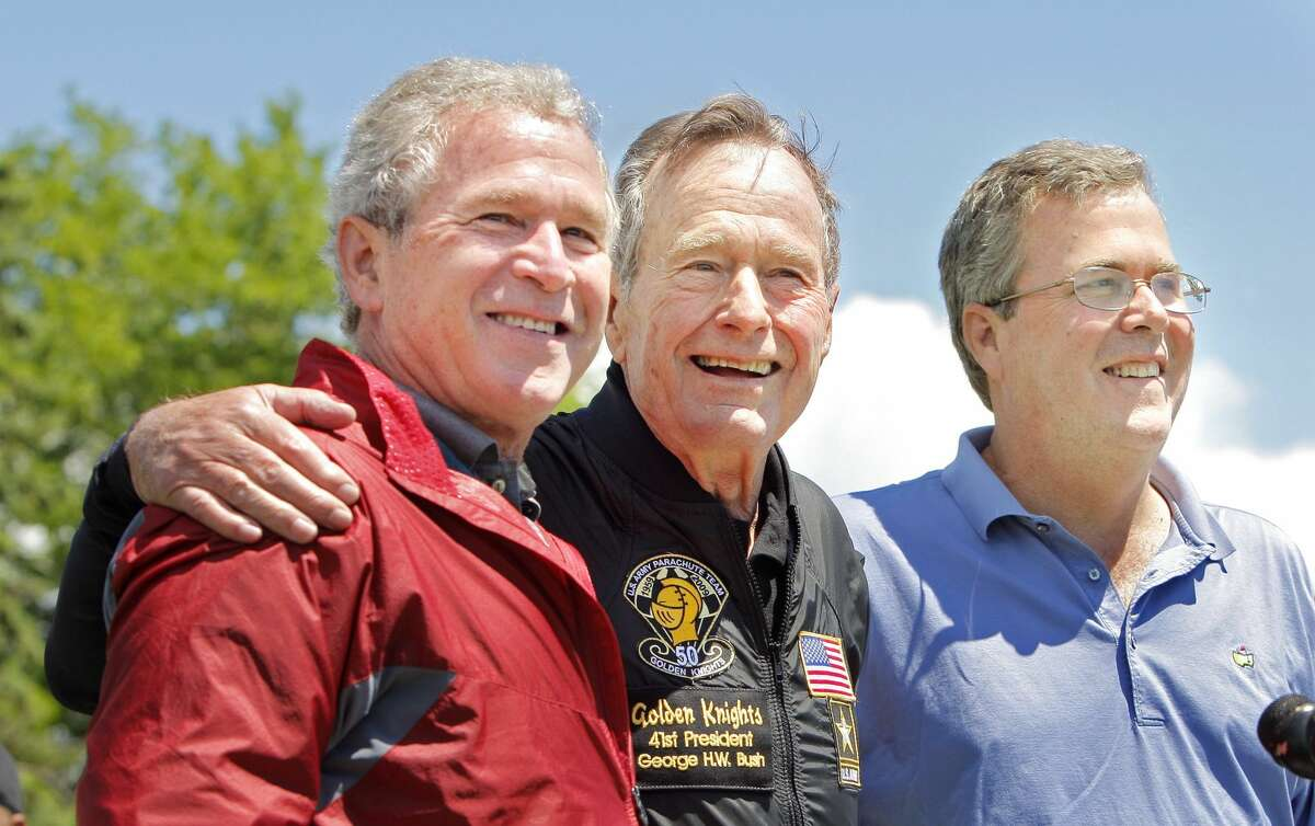 Former President George H. W. Bush poses with his sons former President George W. Bush and Jeb Bush.