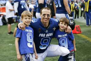 New Orleans Saints Quarterback Drew Brees poses for a picture on the sidelines with his sons, Bowen and Callen during the NFL Pro Bowl Game at Camping World Stadium on January 28, 2018 in Orlando, Florida.