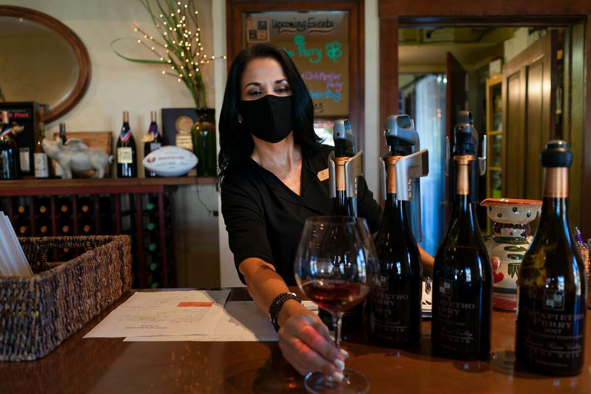 Michelle Taylor wears a mask to serve wine at Papapietro Perry in June 2020. The Healdsburg winery reopens for visitors Jan. 26.
