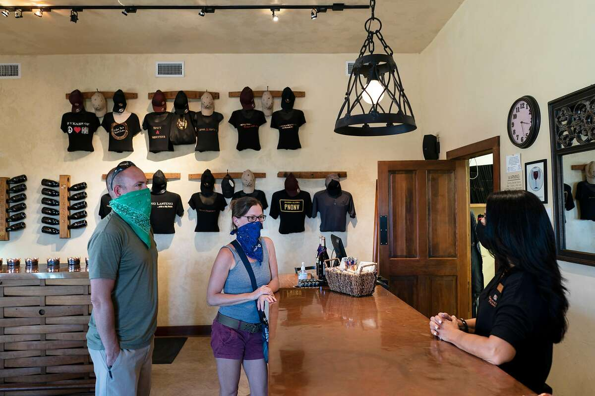 Michelle Taylor wears a mask to serve wine at the Papapietro Perry Winery now that it has reopened its doors. Healdsburg, California on June 18, 2020.