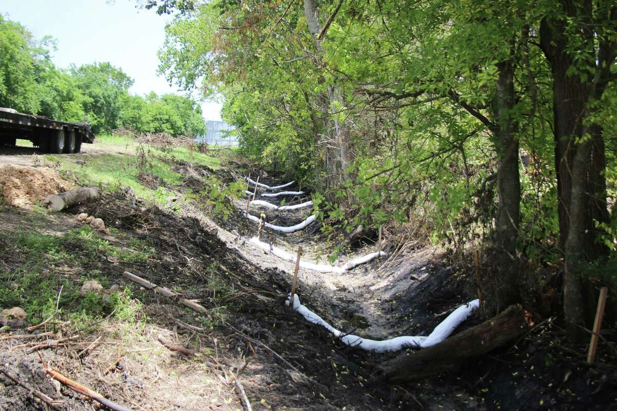 One ditch has boons lined for almost a quarter-of-a-mile where the oily substance has been found. The ditch runs adjacent to a water canal that carries water to several petrochemical facilities, MUD districts, and irrigation customers.