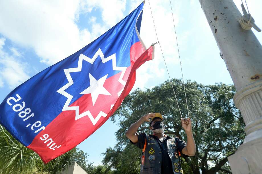 Port Arthur resident and Buffalo Soldiers member Charles Johnson salutes as he helps raise the Juneteenth flag during the first of Port Arthur's Juneteenth celebrations Friday. A crowd gathered outside the courthouse substation for the morning raising of the flag, prayer and comments about the importance of the holiday and the work to be done as we move forward to continue the advancement of true freedom and equality. Photo taken Friday, June 19, 2020 Kim Brent/The Enterprise Photo: Kim Brent/The Enterprise