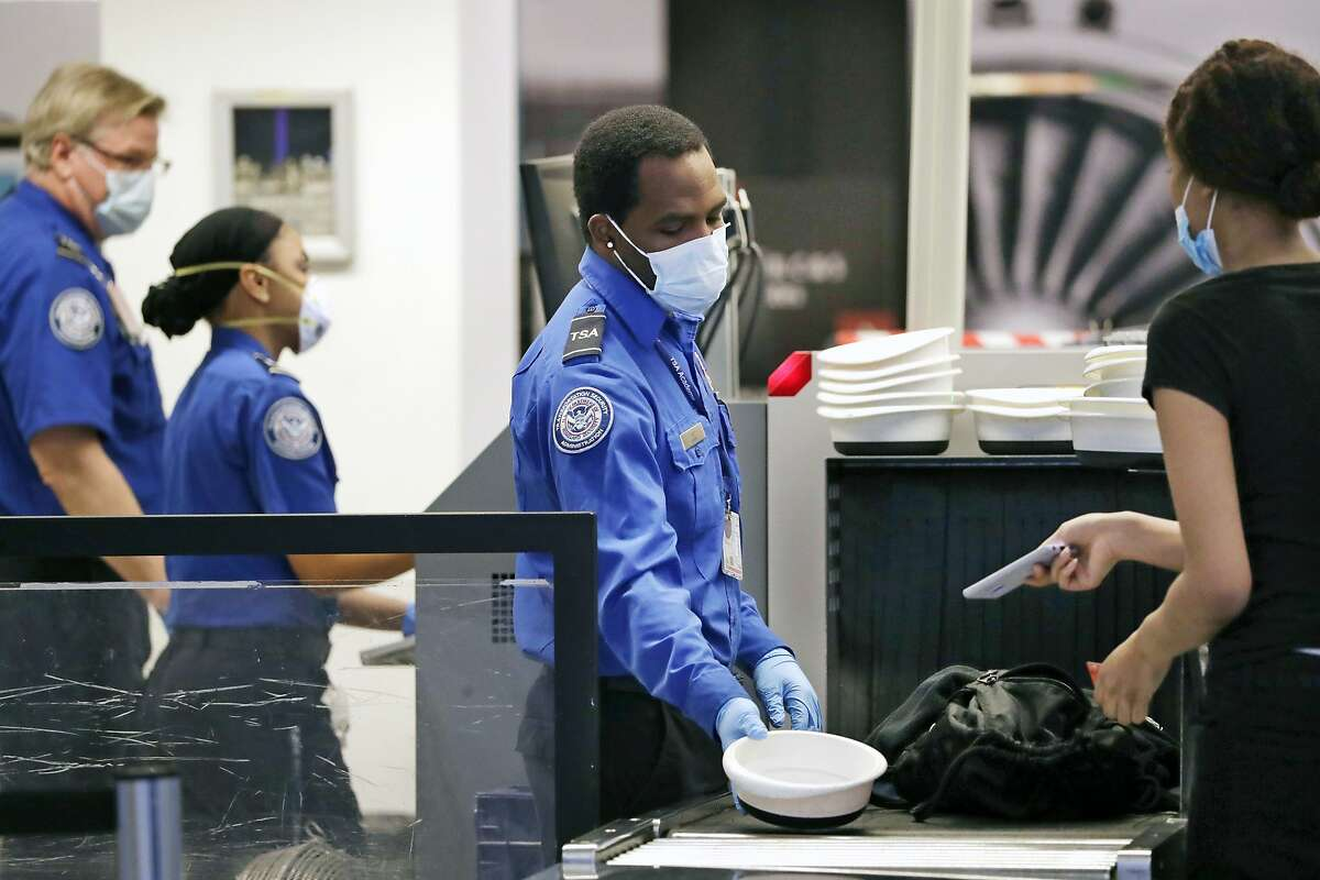 FILE - In this May 18, 2020 file photo TSA officers wear protective masks at a security screening area at Seattle-Tacoma International Airport in SeaTac, Wash. A high-ranking Transportation Security Administration official says the agency is falling short when it comes to protecting airport screeners and the public from the new coronavirus, according to published reports. A federal office that handles whistleblower complaints has ordered an investigation. (AP Photo/Elaine Thompson, File)
