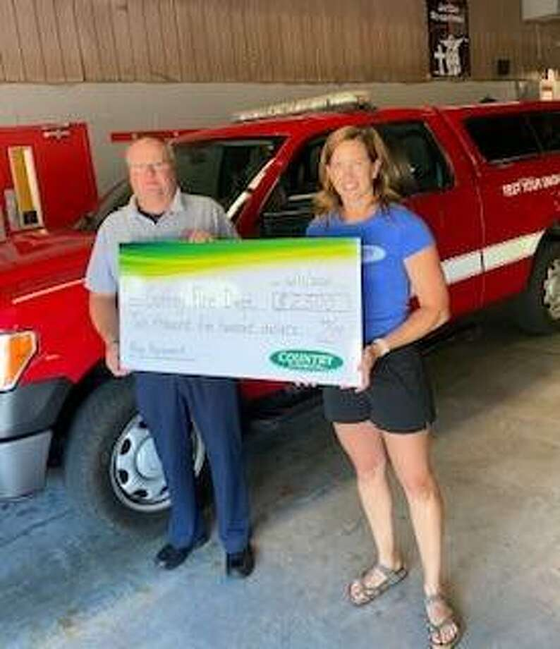 COUNTRY Financial Representative Lindsay Waters, right, presents Godfrey Fire Protection District Chief Eric Cramer with a $2,500 COUNTRY Financial Operation Helping Heroes donation that will be used to help with buying new equipment.