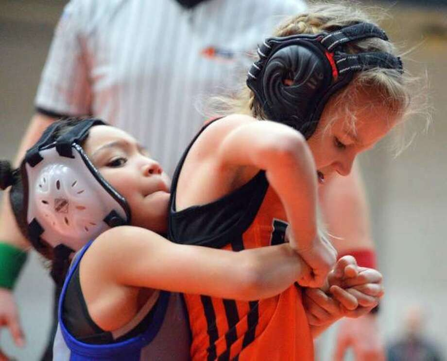 Avery Madison, right, from the Edwardsville Wrestling Club tries to escape her opponent's grasp during a match at the Edwardsville Open on Jan. 11 at Edwardsville High School. Madison, who is 7, competes in the bantam division. Photo: Scott Marion|The Intelligencer
