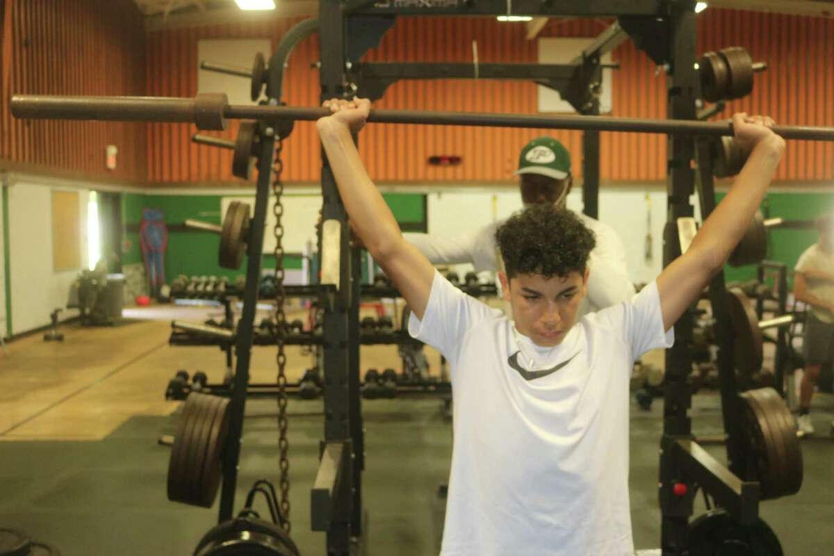 Arnulfo Orozco, Jr. practices how to perform a certain lift without the weights during a Pasadena High School summer conditioning workout Thursday morning.