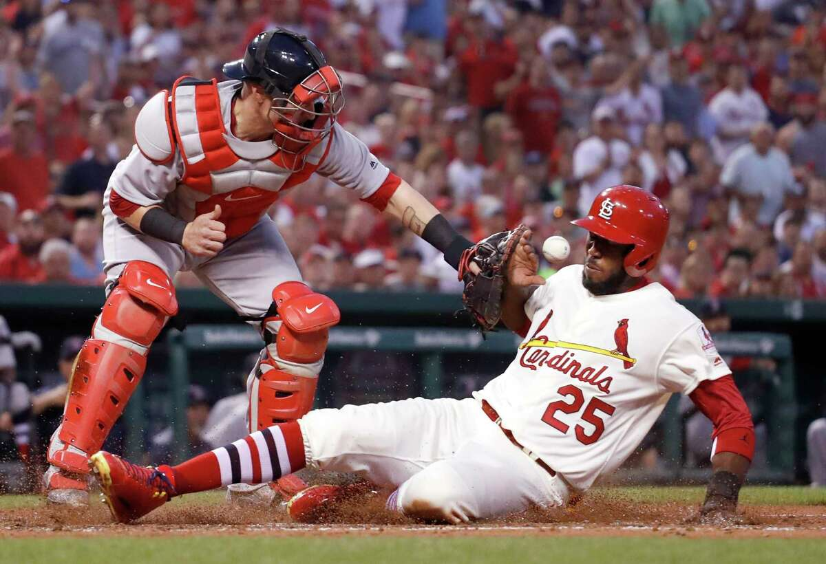 FILE - In this May 16, 2017, file photo, St. Louis Cardinals' Dexter Fowler (25) scores as Boston Red Sox catcher Christian Vazquez is unable to catch the ball during the third inning of a baseball game in St. Louis. Most of the games played between the Red Sox and Cardinals have been in the World Series. If not for the coronavirus pandemic, they would have been playing a regular-season series next weekend at Fenway Park. (AP Photo/Jeff Roberson, File)