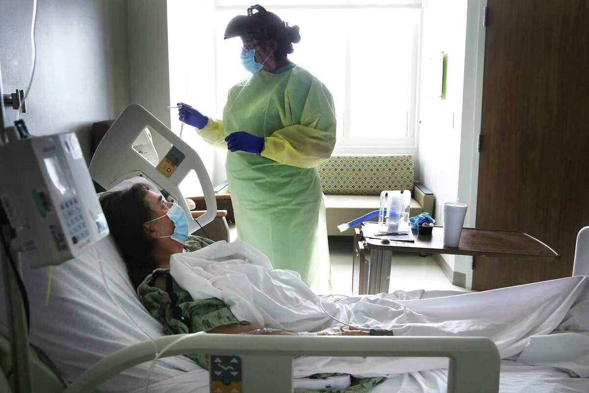 Nurse Olivia Rocha prepares to take the temperature of coronavirus patient Betty Talton at University Hospital in June.