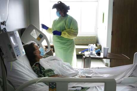 Nurse Olivia Rocha prepares to take the temperature of Betty Talton, who is using a treatment of remdesivir against the coronavirus infection at University Hospital in June. The hospital recently started its third experimental clinical trial.