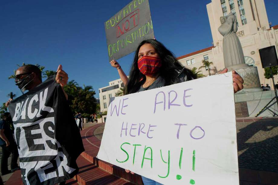 "People hold signs during a rally in support of the Supreme Court's ruling in favor of the Deferred Action for Childhood Arrivals (DACA) program, in San Diego, Calif. June 18. The Supreme Court dealt President Donald Trump's anti-immigration efforts a fresh blow Thursday when it rejected his cancellation of a program protecting 700,000 ""Dreamers,"" undocumented migrants brought to the U.S. as children. Photo: SANDY HUFFAKER / AFP Via Getty Images / AFP or licensors"