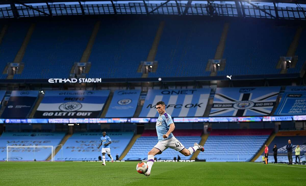 Manchester City's English midfielder Phil Foden crosses the ball in an empty stadium during the English Premier League football match between Manchester City and Arsenal at the Etihad Stadium in Manchester, north west England, on June 17, 2020. - The Premier League makes its eagerly anticipated return today after 100 days in lockdown but behind closed doors due to coronavirus restrictions. (Photo by LAURENCE GRIFFITHS / POOL / AFP) / RESTRICTED TO EDITORIAL USE. No use with unauthorized audio, video, data, fixture lists, club/league logos or 'live' services. Online in-match use limited to 120 images. An additional 40 images may be used in extra time. No video emulation. Social media in-match use limited to 120 images. An additional 40 images may be used in extra time. No use in betting publications, games or single club/league/player publications. / (Photo by LAURENCE GRIFFITHS/POOL/AFP via Getty Images)
