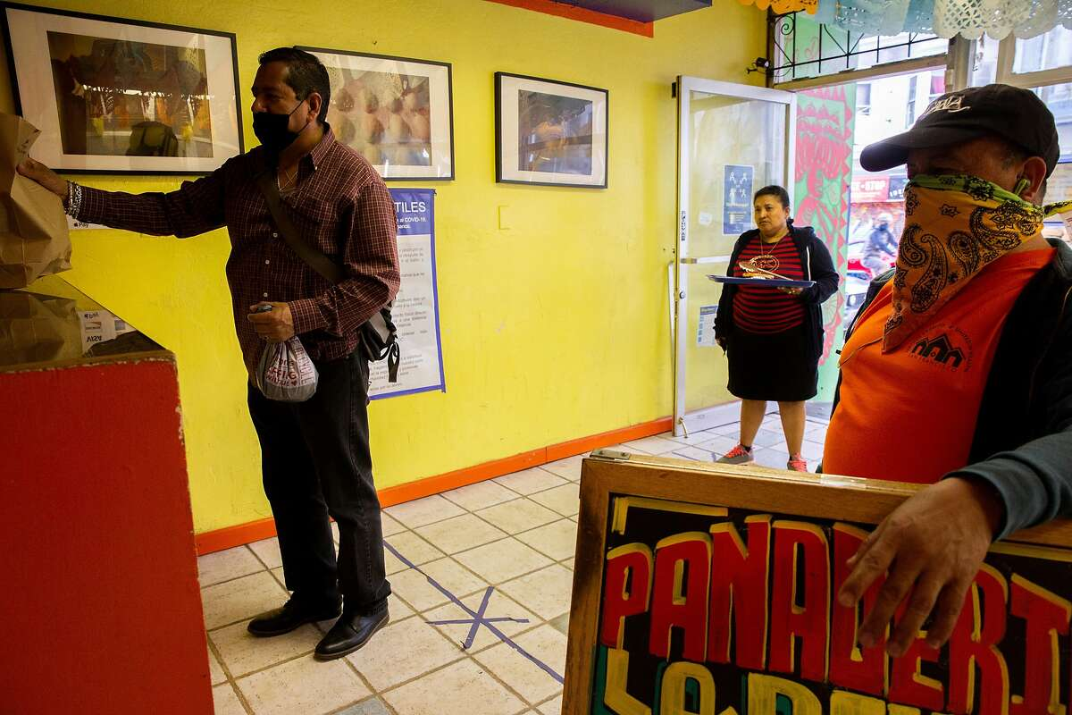 Customers social distance as they wait to complete their purchase at La Reyna Baker on Saturday, April 25, 2020, in San Francisco, Calif.