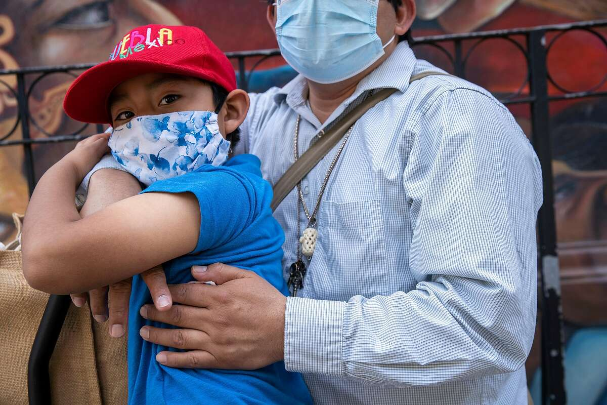 From left: Angel Pascual, 6, is embraced by his father Alejandro Pascual along 24th Street as they wait for Angel's mother to come back from a store, Thursday, May 7, 2020, in San Francisco, Calif. Alejandro was laid off as a restaurant cook after the restaurant boarded up, amid the coronavirus pandemic. Alejandro's partner Asuncion Morales is also without work. They said if they can't get their jobs back or if they can't find a new job soon their savings will deplete within months.