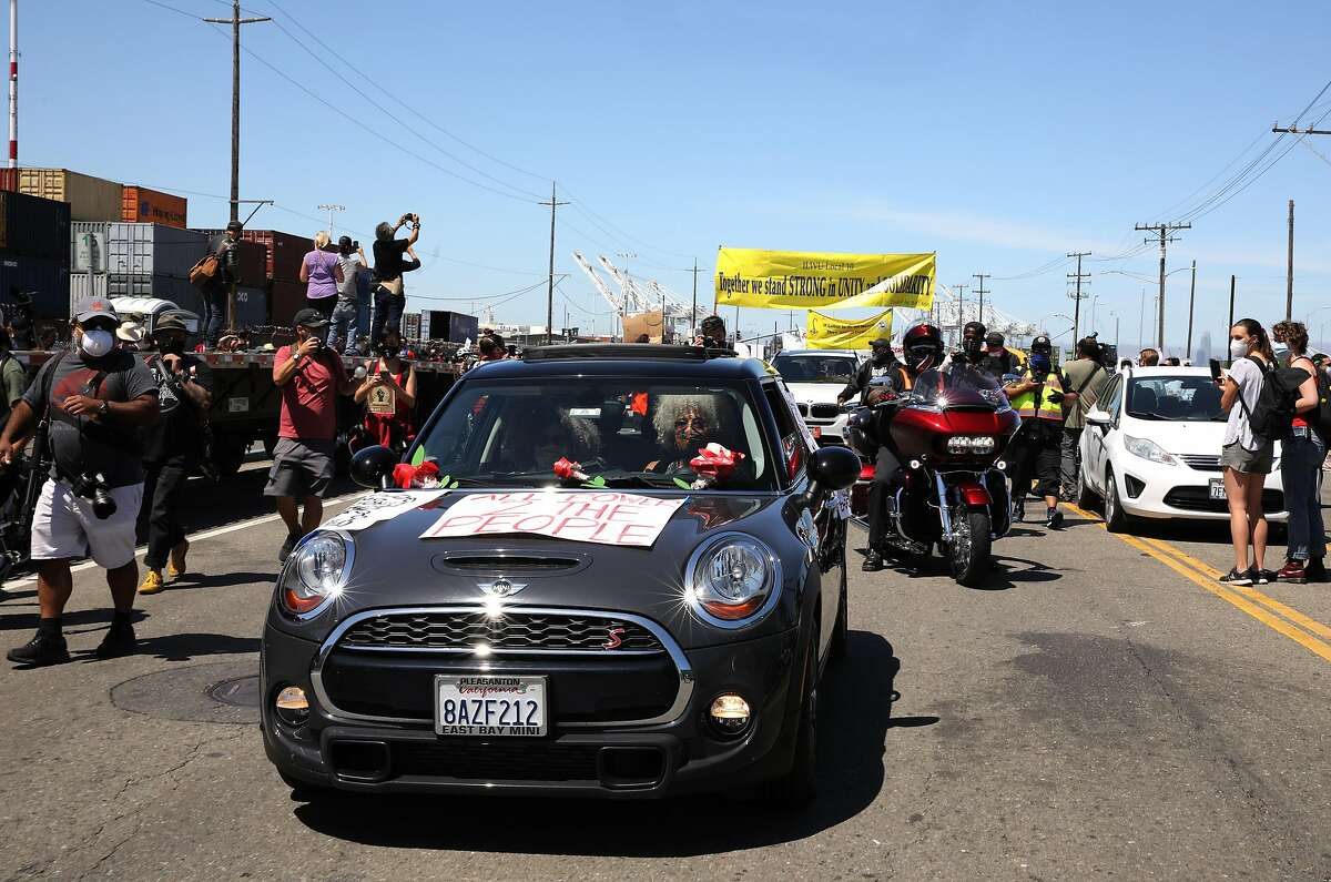 Civil rights icon Angela Davis and her partner Professor Gina Dent ride in their vehicle along Adeline St. while participating in a Juneteenth protest against police brutality as longshoremen shut down the Port of Oakland and 28 other ports along the west coast on Friday, June 19, 2020, in Oakland, Calif.