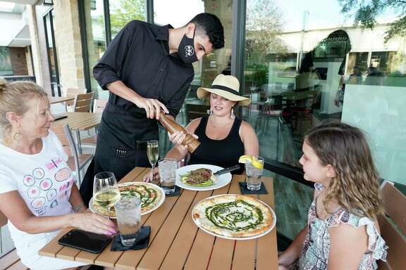 Gabe Rosado, server, adds pepper to dishes at the table of Kitty Weigel, left, Nicole Varick, center, and her daughter, Tinsley Varick 10, at The Union Kitchen, 9920 Gaston Rd., Thursday, June 18, 2020, in Katy.