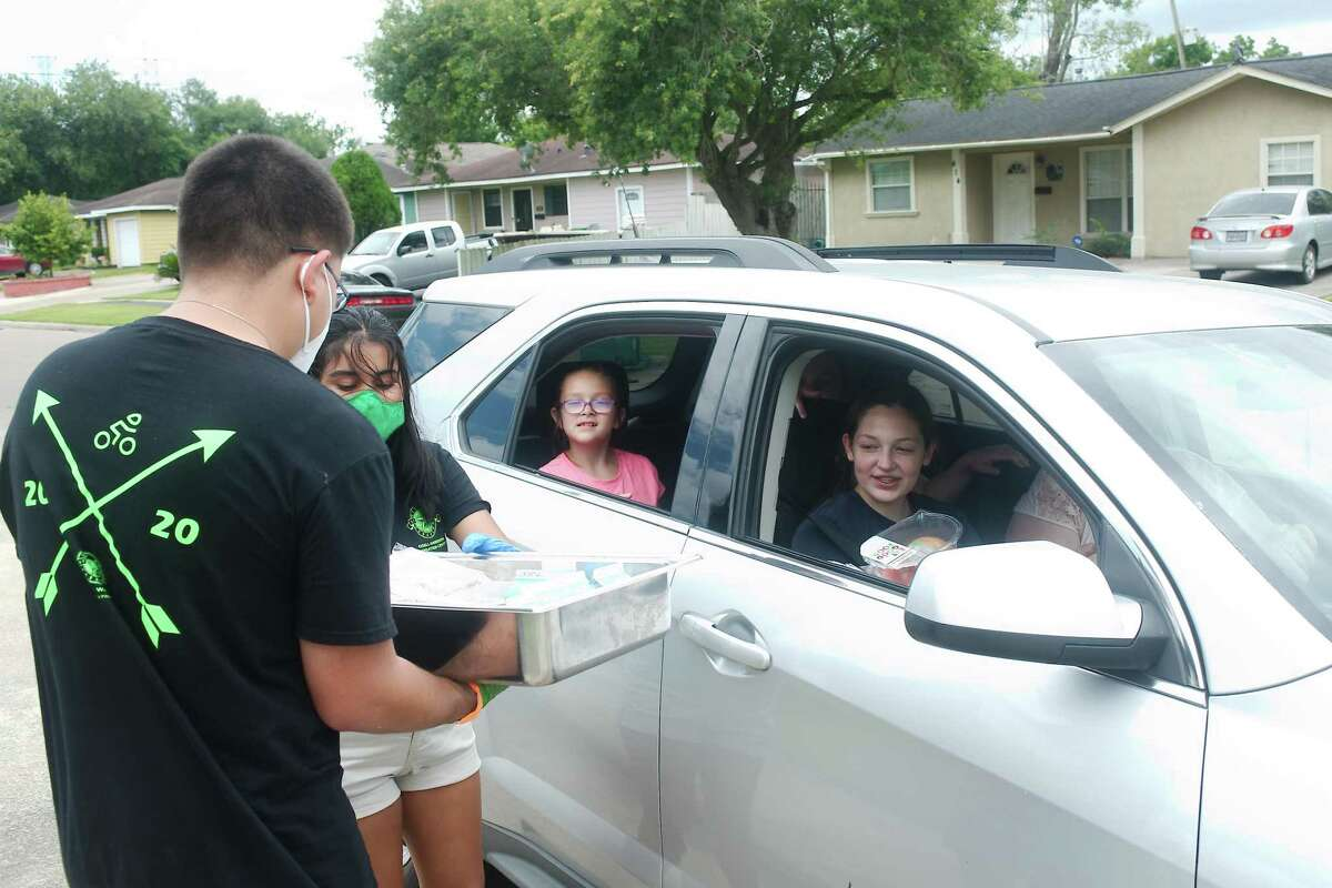 Pasadena Parks and Recreation staff members Rachel Zepeda and Sebastian Garcia provide ready to eat meals and snacks to Emma, Allie and Ryley Kattner. The meals are available to children under the age of 18 free of charge at the center from 1-3 p.m. Monday through Friday.