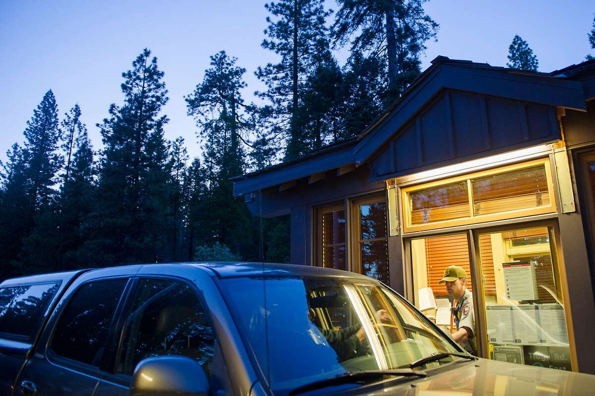 Park ranger James Topputo checks in a visitor at the Big Oak Flat entrance to Yosemite National Park last June. This summer the park is requiring advance reservations to enter.