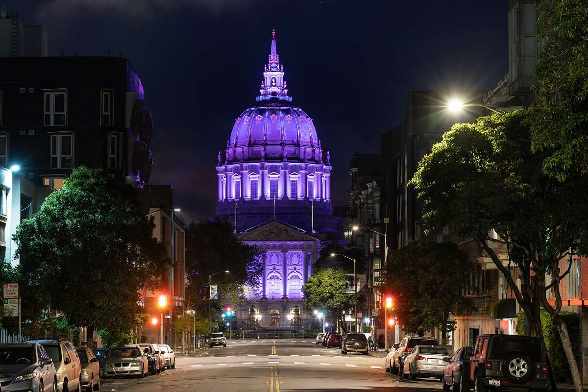 SF City Hall is lighted in purple to honor hospitality workers on Monday, April 6, 2020, in San Francisco, Calif.