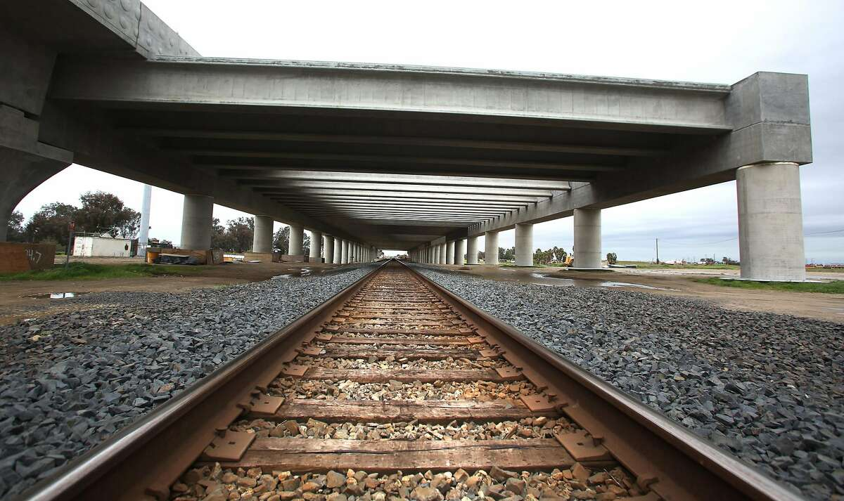 Railroad tracks are overshadowed by a portion of the high speed rail project whcih is shown as it sits waiting to be completed near the San Joaquin River bridge Wednesday, Feb. 13, 2019 in Madera Calif.
