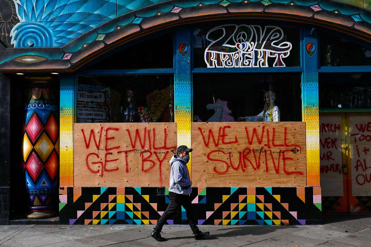 Alex Wolf passes by a store that is boarded-up and written on with supportive messaging on Haight Street on Tuesday, March 17, 2020 in San Francisco, California. The city is ordered to shelter in place due to the coronavirus.