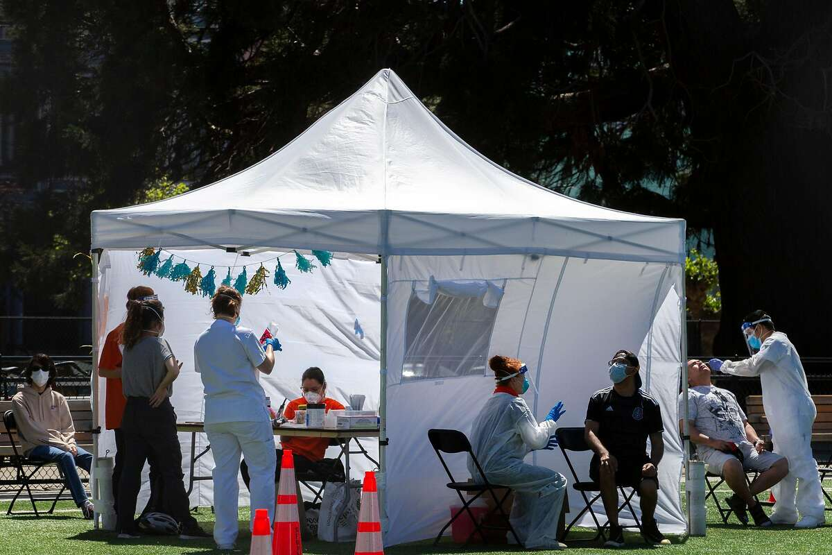 People are tested for COVID-19 at Garfield Park on Tuesday, April 28, 2020, in San Francisco, Calif. The UCSF testing was intended for those in the Mission District with or without symptoms who work or live in the area between Van Ness and Harrison and Cesar Chavez and 23rd. UCSF stated it hopes to ultimately test as many as 5,700 residents to see how many in a sample of the community are infected by or may have recovered from the coronavirus, and to learn how it spreads. UCSF chose the neighborhood for this project, called Unidos en Salud (United in Health), because of its high population density and large Latino population.