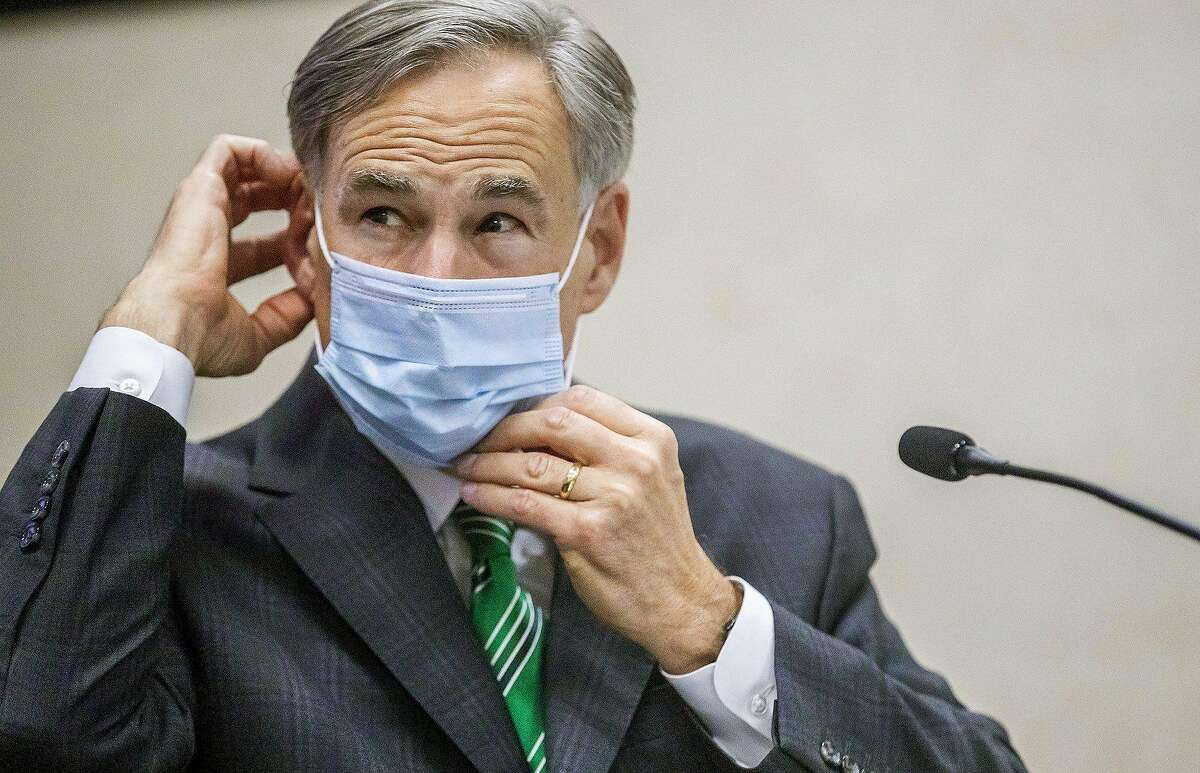 Texas Gov. Greg Abbott adjusts mask during Tuesday update on coronavirus in Texas.