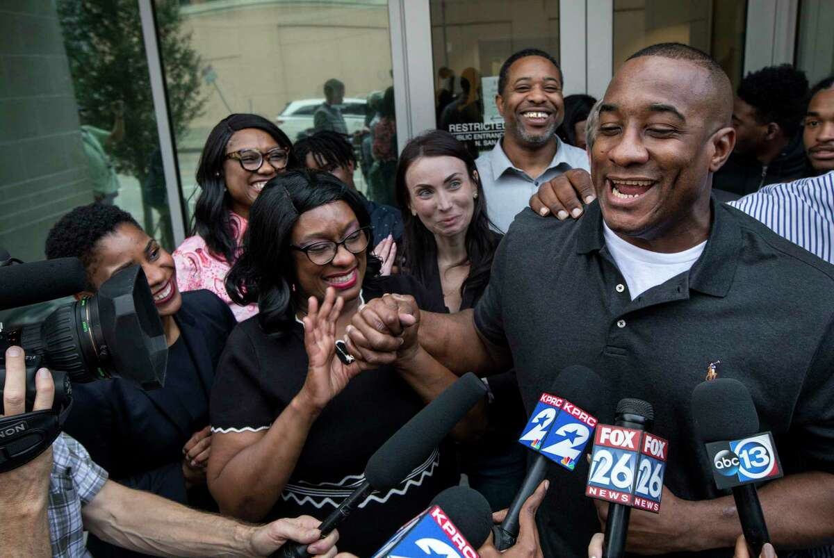 Lydell Grant, right, and his mother Donna Poe, holding his hand, talk to reporters after his release on bond on Tuesday, Nov. 26, 2019, in Houston. Earlier in the day, Grant was ordered released on bond after prosecutors and defense attorneys with the Innocence Project of Texas agreed that Grant should be released while the case is investigated further in light of new DNA evidence. Grant was convicted of capital murder in the 2010 stabbing death of Aaron Scheerhoorn outside of a Montrose bar, and he had spent seven years behind bars.
