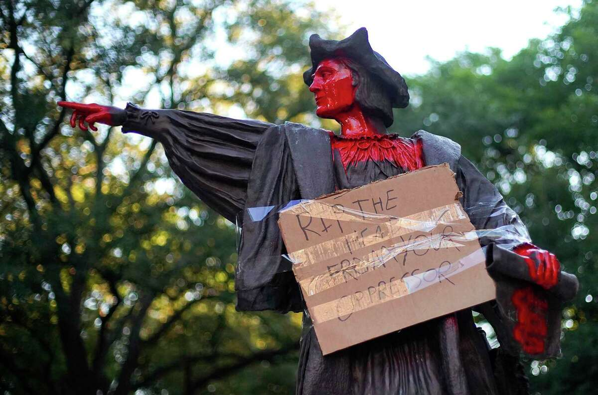 Vandalized statue of Christopher Columbus holds a sign, it hands and head painted red at Bell Park in Houston on Thursday, June 11, 2020.