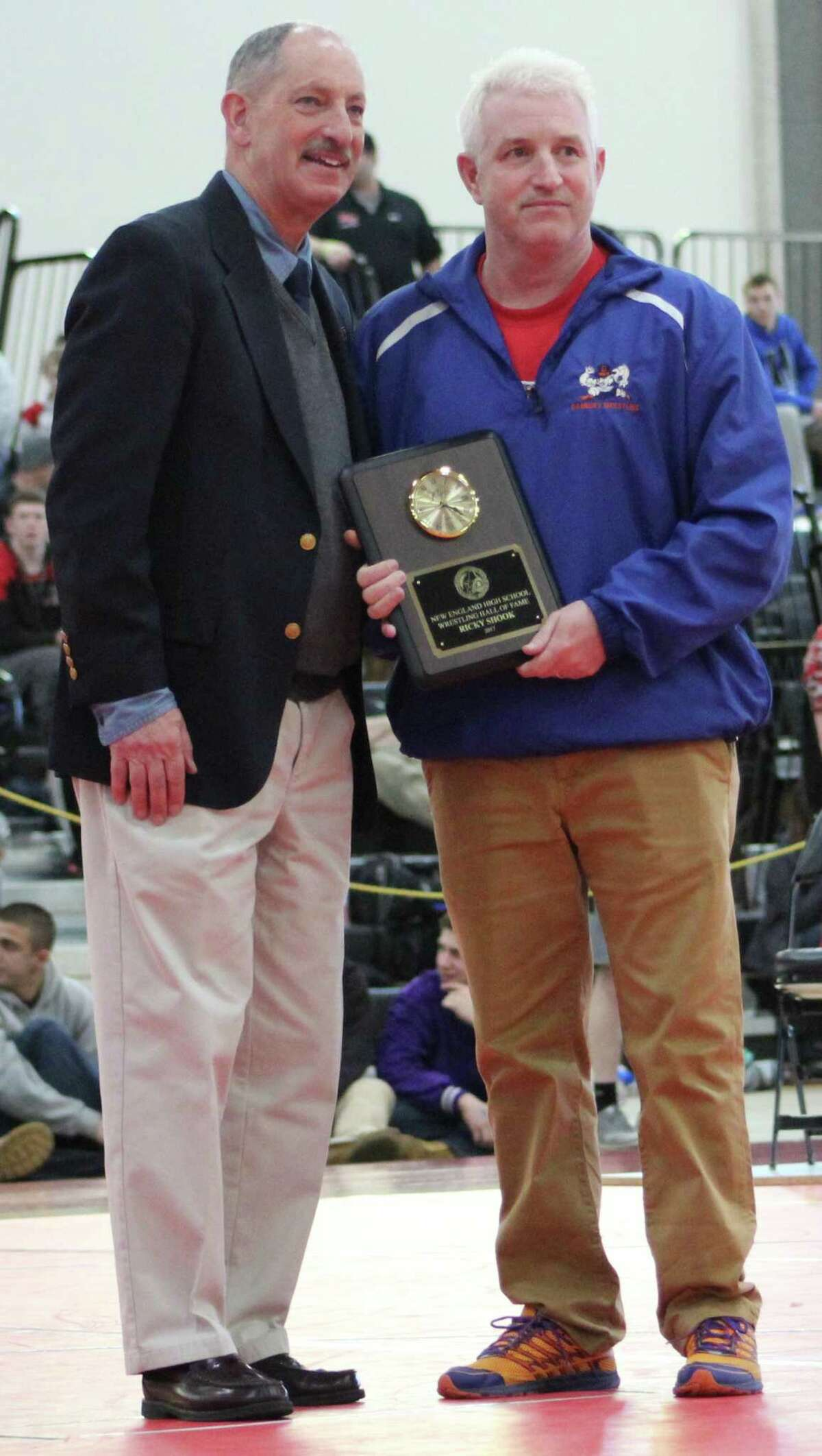 Danbury wrestling coach Ricky Shook, right, is inducted into the New England Wrestling Hall of Fame before the championship matches at the New England championships in March 2017.