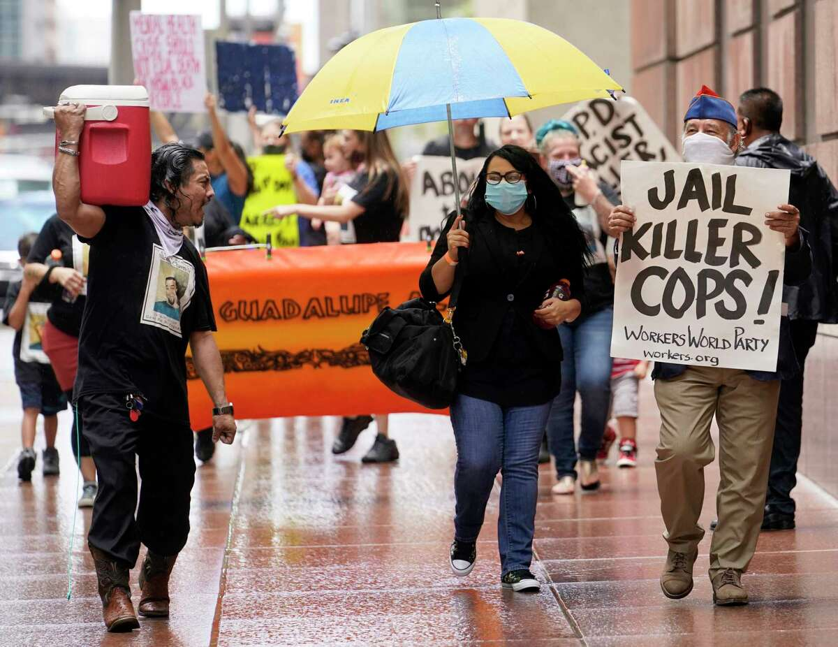 Protesters move along Louisiana St. as they march from City Hall to the Harris County Criminal Courthouse Friday, June 19, 2020, in Houston. The protesters were denouncing the lack of action in the case of Nicolas Chavez, who was shot and killed by Houston police April 21, 2020.