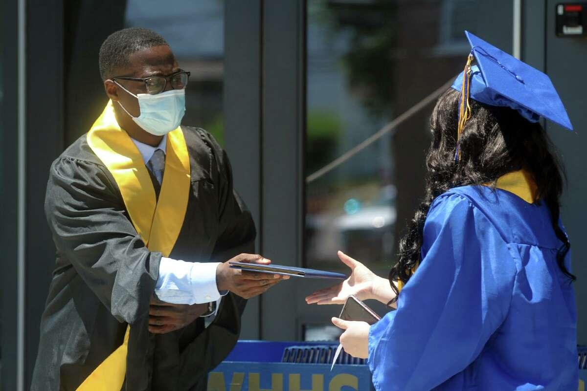 Principal Dan Brown hands out diplomas during graduation for the Harding High School Class of 2020, in Bridgeport, Conn. June 19, 2020.