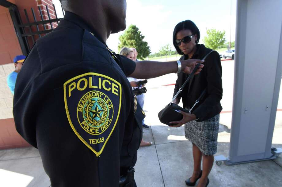 Joseph Malbrough police chief for the Beaumont Independent School District checks the size of associate superintendent Shannon Allen's purse during a demonstration of the district's new metal detectors on Monday. The detectors will be used for large events and are the first to be used for high school sports in the area.   Photo taken Monday, 8/27/18 Photo: Guiseppe Barranco/The Enterprise / Guiseppe Barranco/The Enterprise/ / Guiseppe Barranco ©