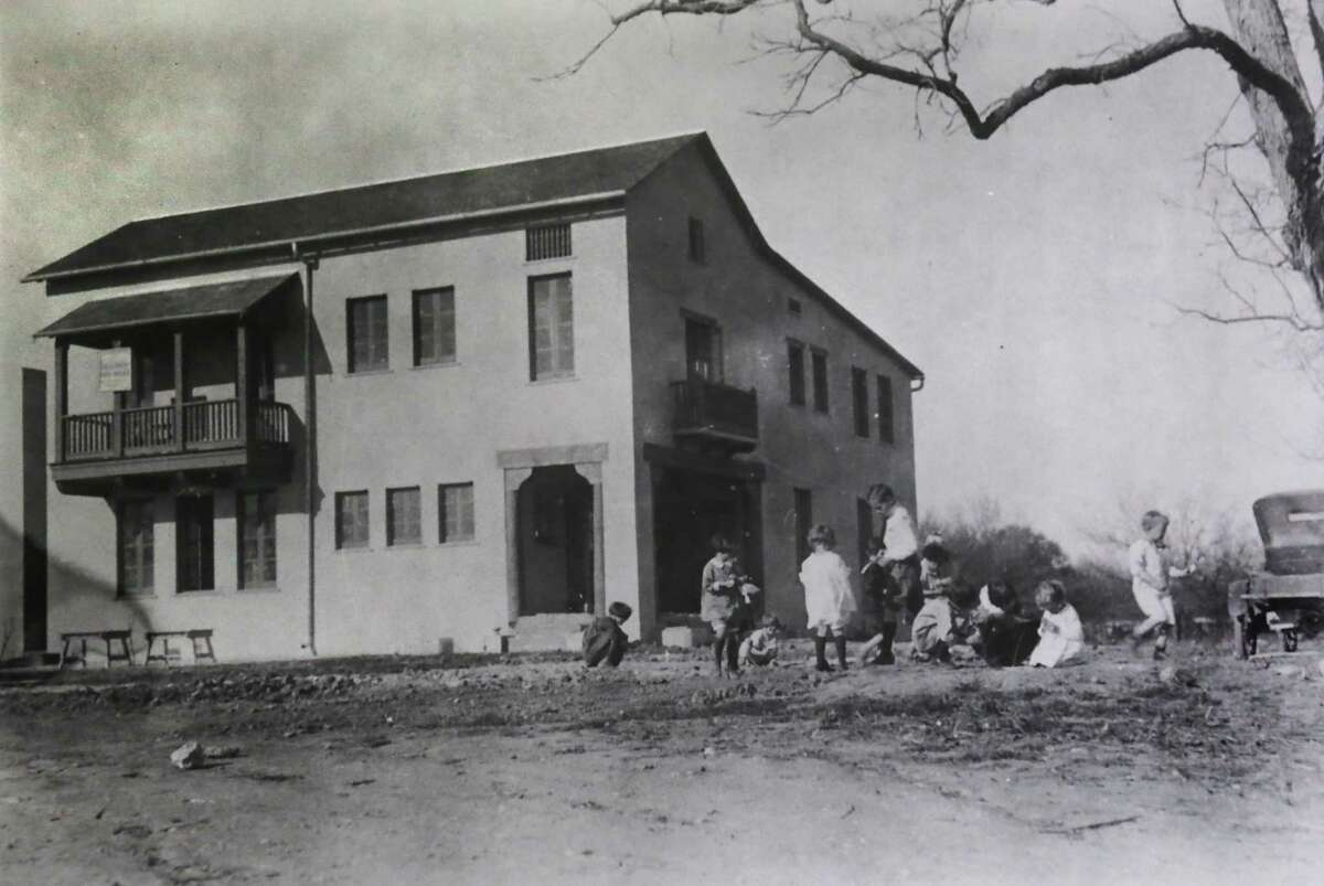 In this historical photo, students play near a school that once was part of the River Road neighborhood. A proposed development there should mesh with the neighborhood's history.