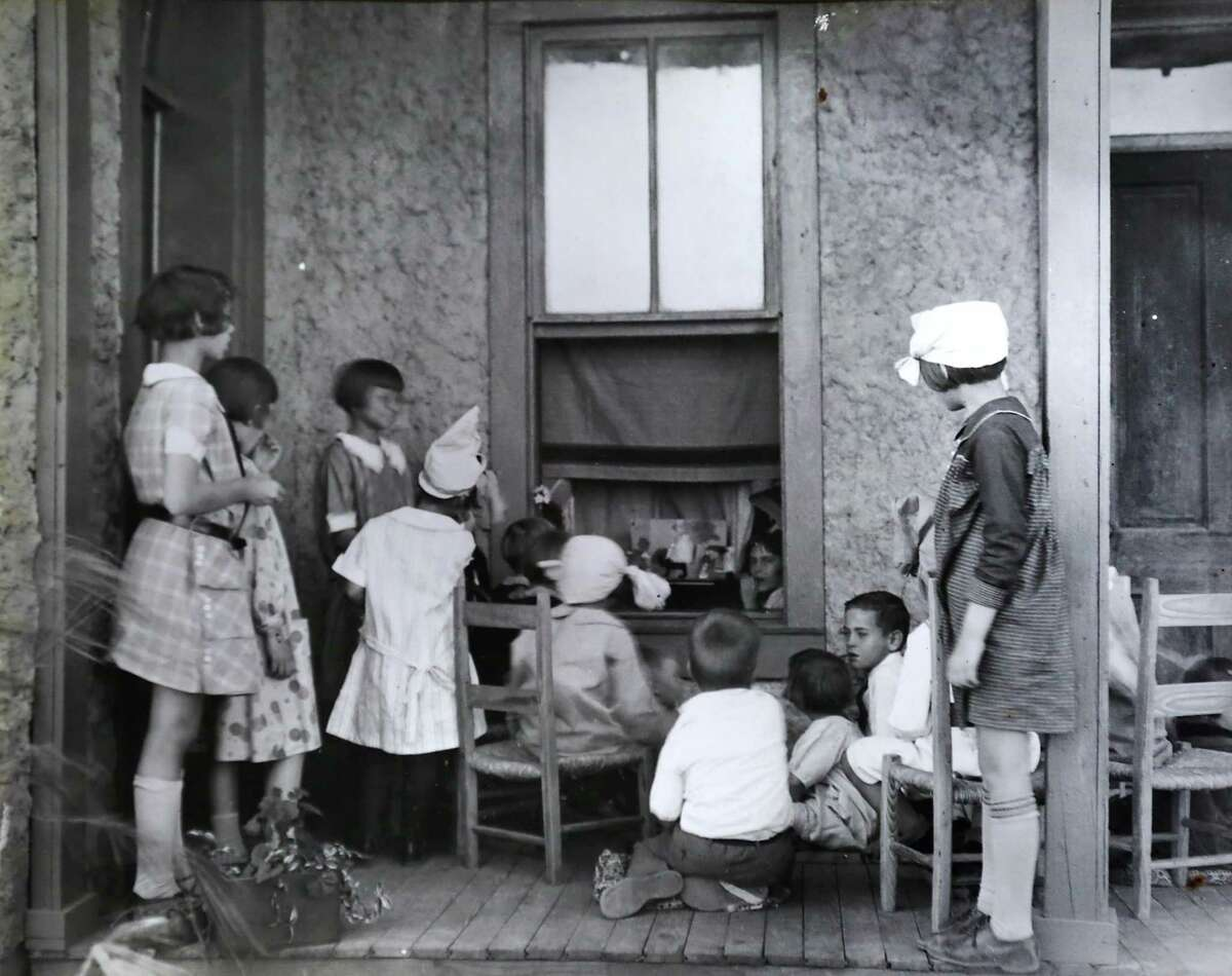 A historical photo showing students watching a play on a porch through an open window, of a school that later was the home of Donna Cloud and the late musician Jim Cullum in the River Road Historic District, near Brackenridge Park.