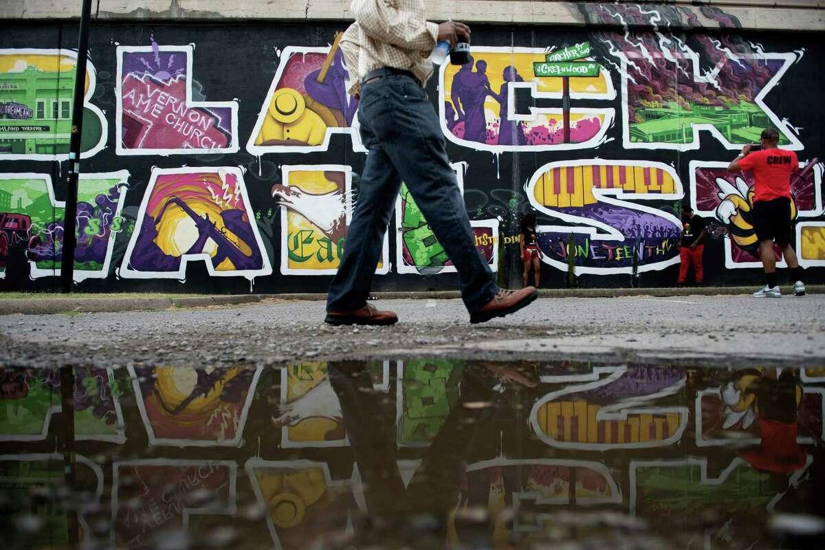 People walk near a Black Wall Street mural in the Greenwood District in Tulsa, Oklahoma.