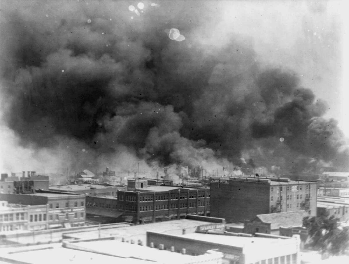 """In this 1921 image provided by the Library of Congress, smoke billows over Tulsa, Okla. For decades, when it was discussed at all, the killing of hundreds of people in a prosperous black business district in 1921 was referred to as the Tulsa race riot. Under new standards developed by teachers for approaching the topic, students are encouraged to consider the differences between labeling it a """"massacre"""" instead of a """"riot,"""" as it is still commemorated in state laws."""